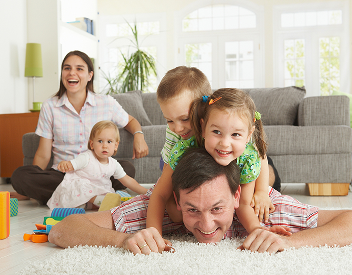 Happy family having fun on floor of in living room at home, laug