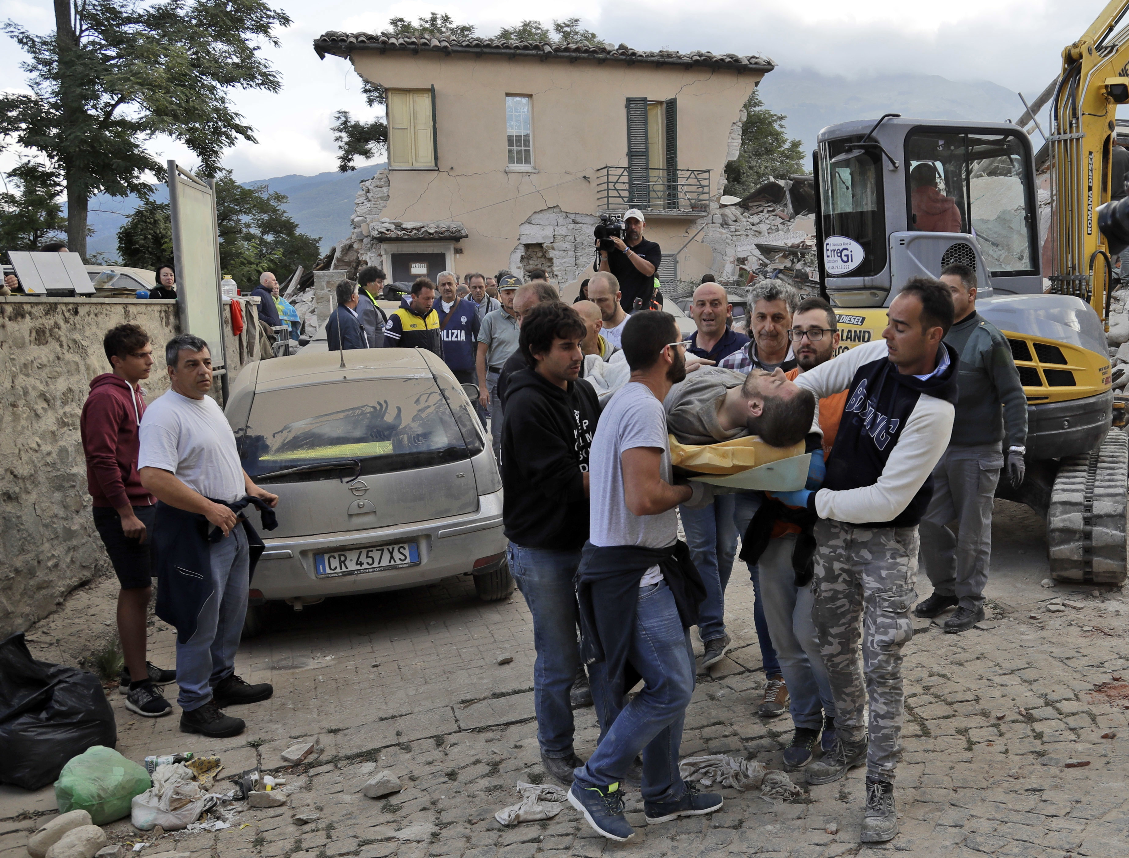 A man is carried out on a stretcher as a collapsed building is seen in the background following an earthquake, in Amatrice, Italy, Wednesday, Aug. 24, 2016.  The magnitude 6 quake struck at 3:36 a.m. (0136 GMT) and was felt across a broad swath of central Italy, including Rome where residents of the capital felt a long swaying followed by aftershocks. (AP Photo/Alessandra Tarantino)