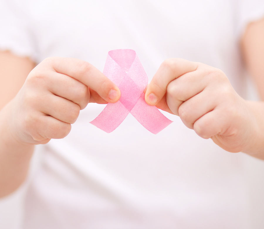 Healthcare and medicine concept - girl hands holding pink breast cancer awareness ribbon ** Note: Soft Focus at 100%, best at smaller sizes